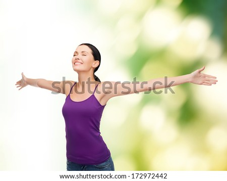 happiness and people concept - smiling girl in blank purple tank top waving hands with closed eyes - stock photo