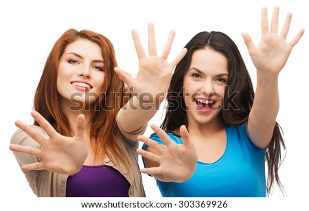 happiness and people concept - two smiling girls showing their palms - stock photo