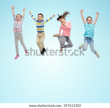 happiness, childhood, freedom, movement and people concept - happy little children jumping in air over blue background - stock photo