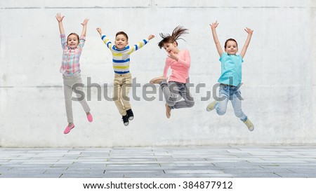 happiness, childhood, freedom, movement and people concept - happy little girl jumping in air over concrete wall on street background - stock photo