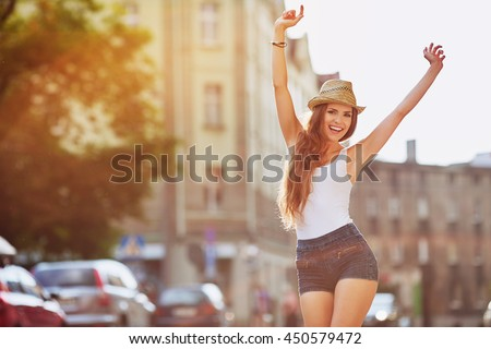 Happiness concept - happy woman having fun on city street during summer