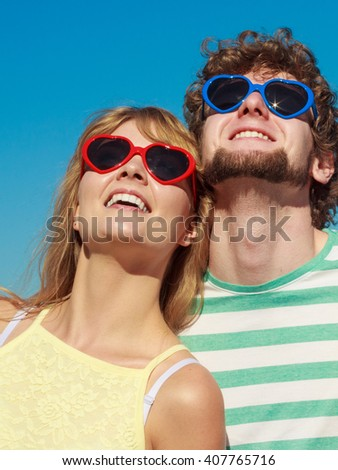 Happiness dating concept. Couple in love wearihg heart shaped sunglasses, blonde woman bearded man enjoy romantic date outdoor