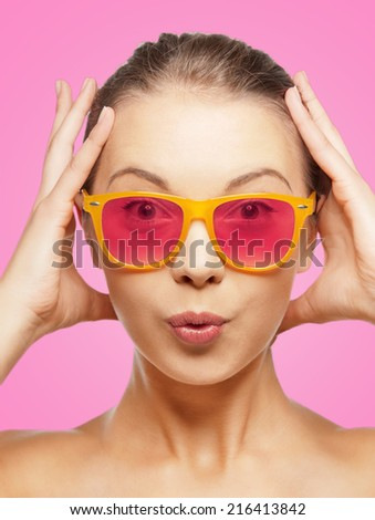 happiness, face expressions and people concept - portrait of surprised teenage girl in pink sunglasses - stock photo