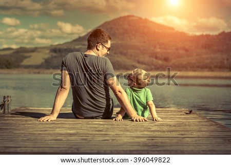 Happiness father and son on the pier at sunny day under sunlight. - stock photo