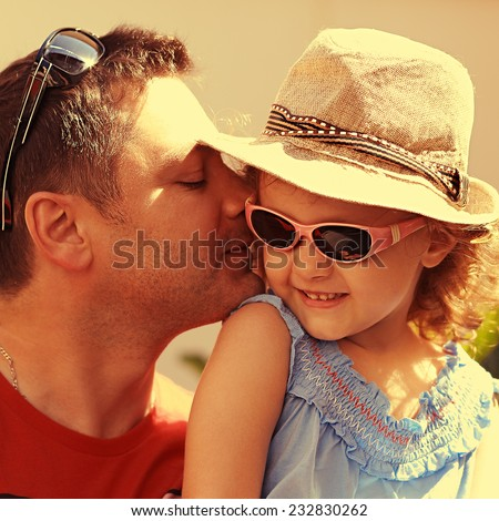 Happiness. Father kissing his daughter outdoors summer background. Closeup portrait - stock photo