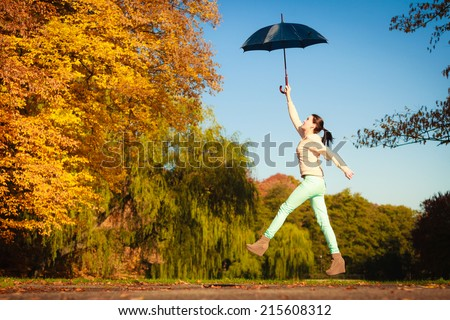 Happiness freedom and people concept. Casual young woman teen girl jumping with blue umbrella in autumnal park, having fun outdoor - stock photo