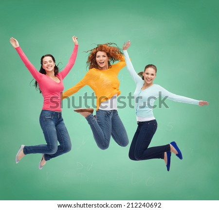 happiness, freedom, friendship, education and people concept - smiling young women jumping in air over green board background - stock photo
