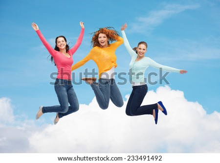happiness, freedom, friendship, movement and people concept - group of smiling young women jumping in air over blue sky with white cloud background - stock photo