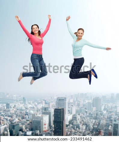 happiness, freedom, friendship, movement and people concept - smiling young women jumping in air over city background - stock photo