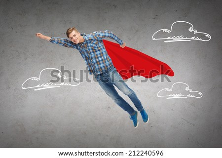 happiness, freedom, movement and people concept - smiling young man flying in air over blue background concrete wall with drawing of clouds background - stock photo