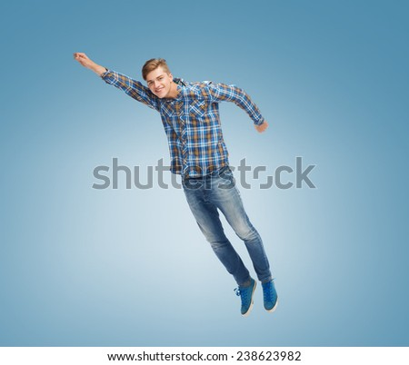 happiness, freedom, movement and people concept - smiling young man flying in air over blue background - stock photo