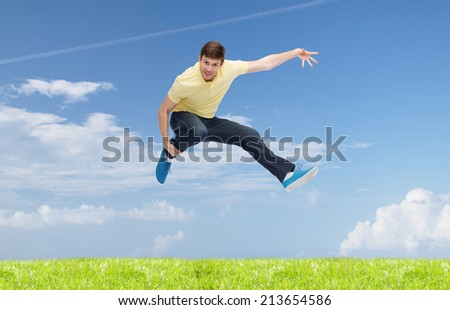 happiness, freedom, vacation, summer and people concept - smiling young man jumping in air over natural background