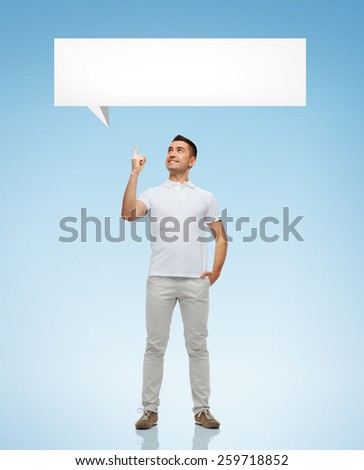 happiness, gesture and people concept - smiling man pointing finger up to white blank text bubble over blue background - stock photo