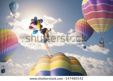 Happiness girl jumping over hot air balloon - stock photo
