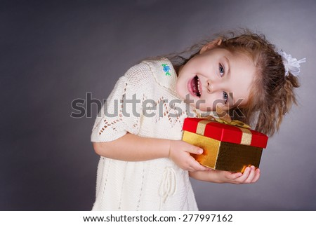 Happiness girl with red gift in her hands, work in studio - stock photo
