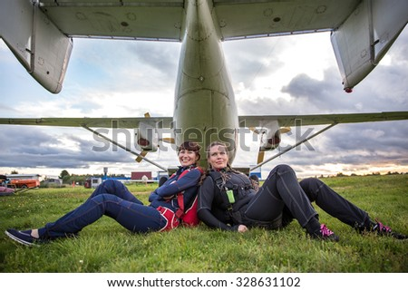 happiness girlfriend parachutist rest under the wing of the aircraft on the grass