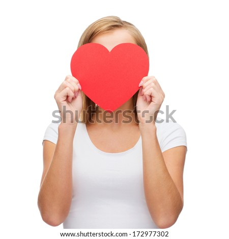happiness, health and love concept - woman in white t-shirt covering her face with red heart