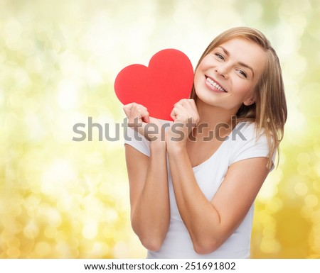 happiness, health, people, holidays and love concept - smiling young woman in white t-shirt holding red heart over yellow lights background - stock photo