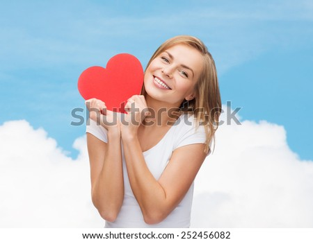 happiness, health, people, holidays and love concept - smiling young woman in white t-shirt holding red heart over blue sky with cloud background - stock photo
