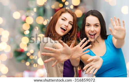 happiness, holidays, friendship and people concept - smiling teenage girls having fun over christmas tree background - stock photo
