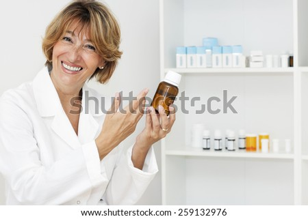 Happiness mature female pharmacist looking at camera and showing a bottle of pills in the pharmacy. - stock photo