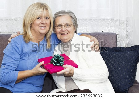 Happiness Mature nurse embracing  senior woman and holding Christmas gift while sitting on the sofa. - stock photo