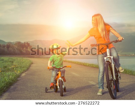 Happiness Mother and son on the bicycles fun outdoors. - stock photo