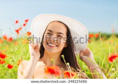 happiness, nature, summer, vacation and people concept - smiling young woman wearing straw hat on poppy field - stock photo