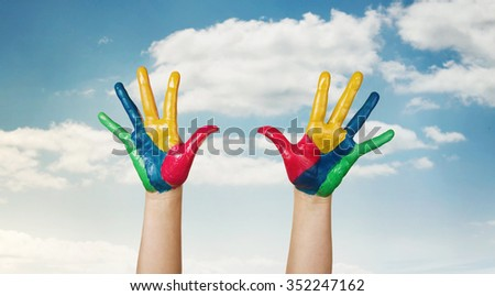 Happiness, painted colorful child's hands against the sky with copy space - stock photo