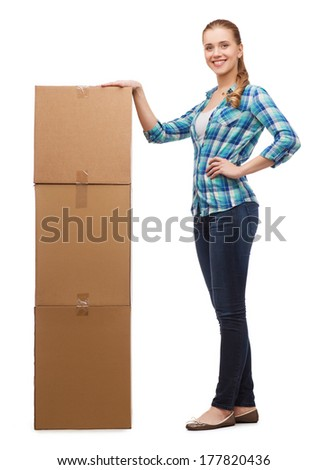 happiness, postal and people concept - smiling young woman standing next to tower of boxes
