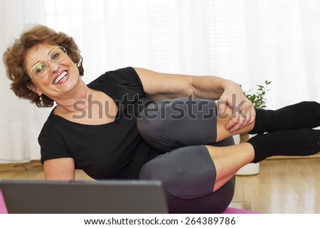 Happiness senior brown haired woman  lying on the parquet floor looking at camera and  exercising yoga at home. - stock photo