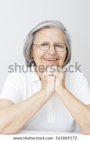 Happiness senior woman with hands on her chin looking at camera. - stock photo