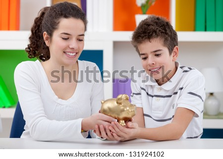 Happiness sister and brother holding gold piggybank, - stock photo