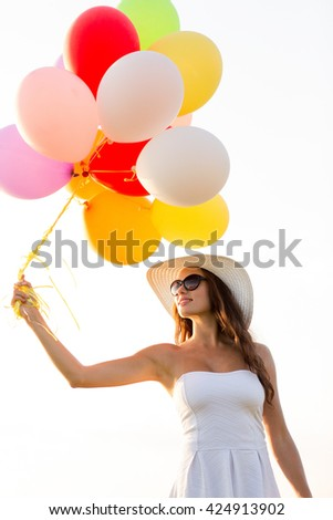 happiness, summer, holidays and people concept - smiling young woman wearing sunglasses with balloons outdoors - stock photo