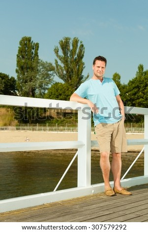 Happiness summer vacation and people concept. Fashion portrait of handsome man on pier
