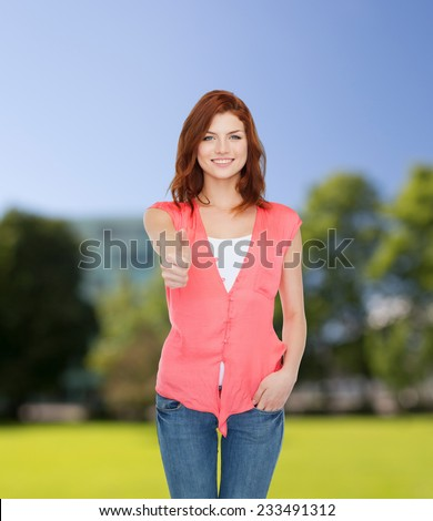 happiness, summer vacation, gesture and people concept - smiling teenage girl in casual clothes showing thumbs up over park background - stock photo