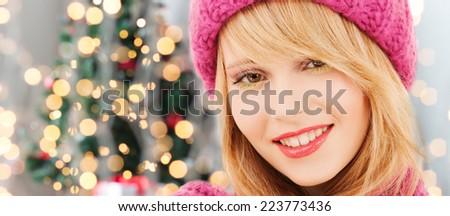 happiness, winter holidays and people concept - close up of smiling young woman in pink hat and scarf over christmas tree lights background - stock photo