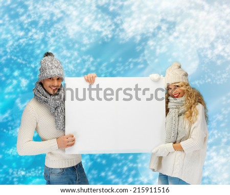 happiness, winter holidays, christmas, advertising and people concept - smiling couple in winter clothes holding big white blank board over blue snowy background - stock photo