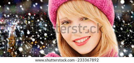 happiness, winter holidays, christmas and people concept - close up of smiling young woman in pink hat and scarf over snowy night city background - stock photo