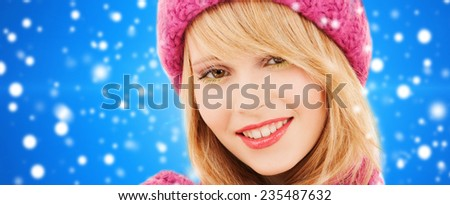 happiness, winter holidays, christmas and people concept - close up of smiling young woman in pink hat and scarf over blue snowy background