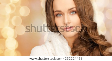 happiness, winter holidays, christmas and people concept - close up of smiling young woman in white warm clothes over beige lights background
