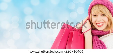 happiness, winter holidays, christmas and people concept - smiling young woman in hat and scarf with pink shopping bags over blue lights background - stock photo