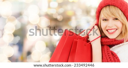happiness, winter holidays, christmas and people concept - smiling young woman in hat and scarf with red shopping bags over lights background - stock photo