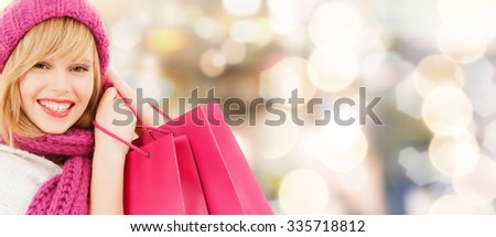 happiness, winter holidays, christmas and people concept - smiling young woman in hat and scarf with pink shopping bags over lights background - stock photo