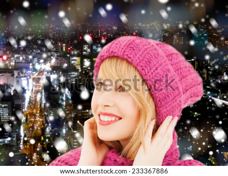 happiness, winter holidays, christmas and people concept - smiling young woman in pink hat and scarf over blue snowy background - stock photo