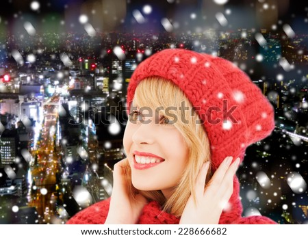 happiness, winter holidays, christmas and people concept - smiling young woman in red hat and scarf over blue snowy background - stock photo
