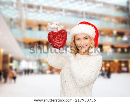 happiness, winter holidays, christmas and people concept - smiling young woman in santa helper hat with red heart decoration over shopping center background - stock photo