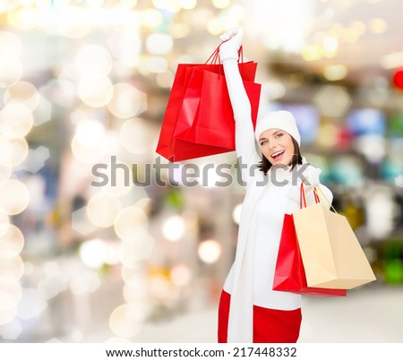 happiness, winter holidays, christmas and people concept - smiling young woman in white hat and mittens with red shopping bags over lights background