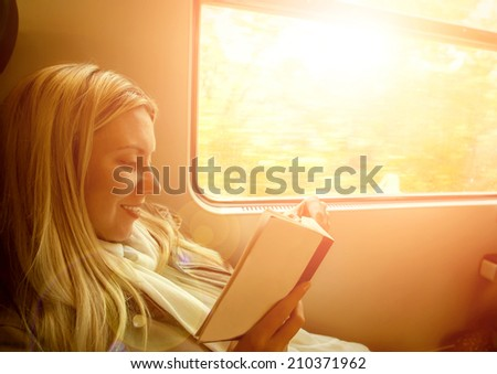 Happiness woman reading book in train under sunlight - stock photo