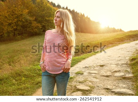 Happiness woman stay outdoor under sunlight of sunset - stock photo